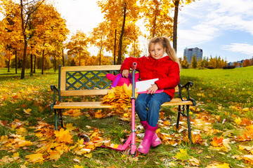 Little blond girl sitting on the bench in park