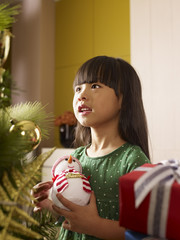 little girl standing in front of christmas tree and dreaming