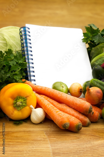 Different fresh vegetables with empty cookbook