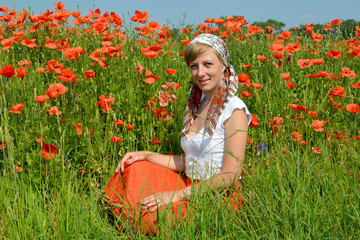 The young woman sits on a grass in a poppy field