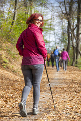 Sportive cute woman Nordic walking autumn cross country