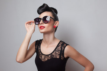 Young fashionable woman in round sunglasses