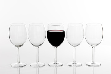 Glass of red wine in a row of empty glasses