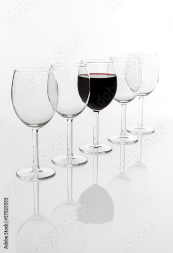 Glass filled with red wine in a row of empty glasses