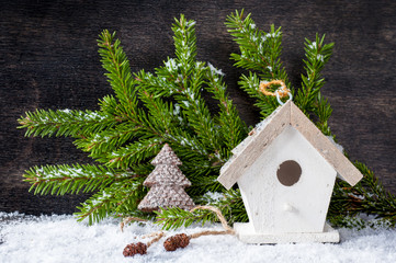 Сhristmas tree decoration and birdhouse on a wooden background