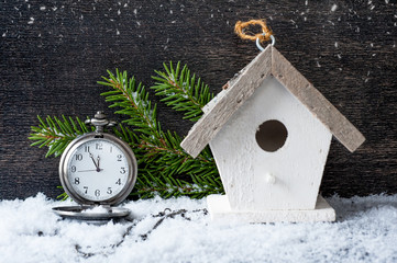Christmas antique clock and a birdhouse on a wooden background