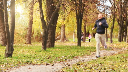 Male runner jogging in park in autumn park forest in fall colors
