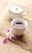 cup of tea with beautiful orchid over wooden background
