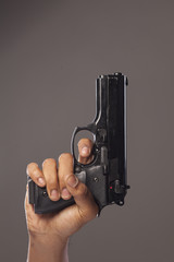 dark skinned man's hand with a gun
