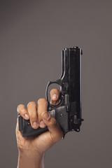 dark skinned man's hand with a gun