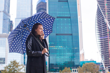 Fashion young woman talking on the phone with an umbrella in