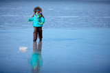 Cute little boy outdoors playing on frozen sea poster