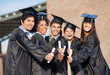Students In Graduation Gowns Showing Diplomas On Campus - 57831832