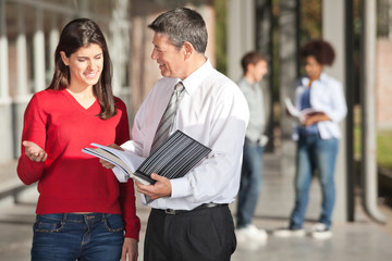 Teacher And Student Discussing Over Book On Campus