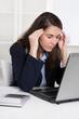 Burnout - Frau hat Migräne - sitzend am Schreibtisch; Arbeit