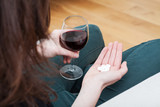 Woman with drugs and glass of wine