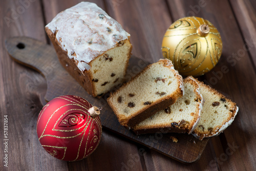Sliced christmas fruit-cake and xmas balls, high angle view