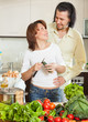 A man and a woman with vegetables in the kitchen