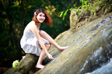 Young asian woman enjoying the pure waters of a mountain river i