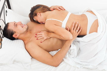 Smiling lovers in bed