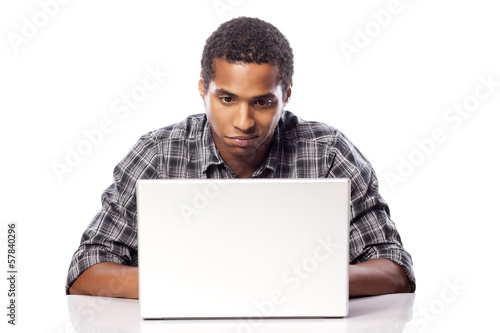 dark-skinned young man uncertainly looking at his laptop