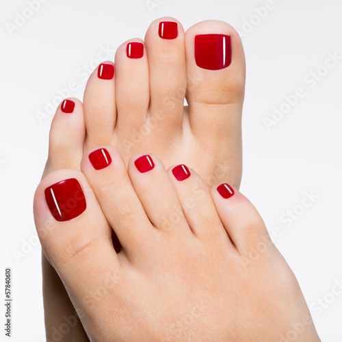 Beautiful female feet with red pedicure