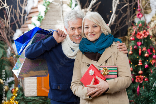 Couple With Shopping Bags And Present At Christmas Store