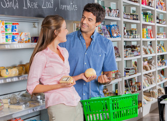 Woman Looking At Man While Buying Cheese