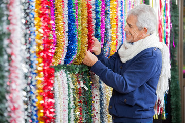 Man Choosing Tinsels In Christmas Store
