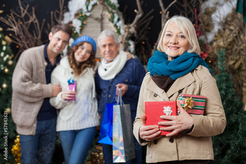 Happy Family With Christmas Presents At Store