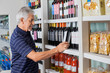 Senior Man Choosing Wine At Supermarket