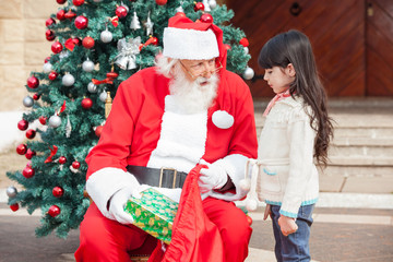 Santa Claus Giving Gift To Girl