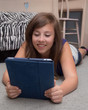 Cute teenage girl reading from electronic tablet