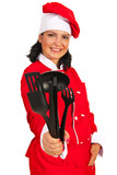 Happy chef woman giving kitchen utensils