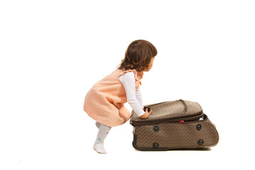 Toddler girl pushing luggage