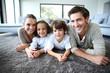 Leinwanddruck Bild - Family at home relaxing on carpet