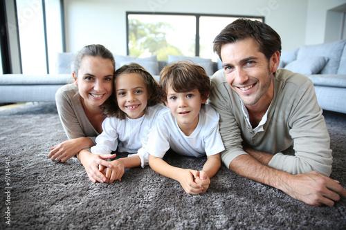 Leinwanddruck Bild Family at home relaxing on carpet