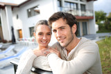 Fototapety Couple standing outside in front of new home