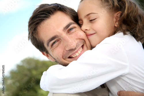 Little girl kissing her dad on cheek
