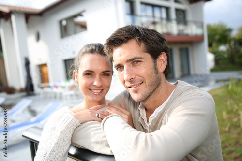 Couple standing outside in front of new home