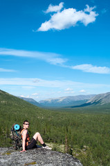 Man hiker with backpack sitting on top and looking at camera