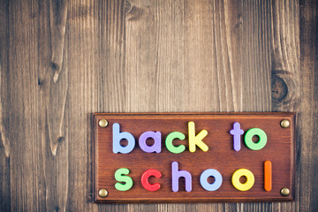 Back to school sign board of color letters on wooden background