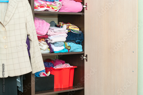 Various color clothes are organized at shelves in open wardrobe