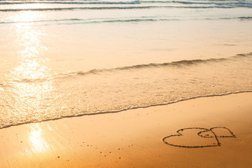 Hearts drawn on the sand of a beach, soft wave of the sea