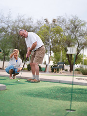 senior couple playing mini golf