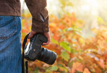 Photographer holding camera outdoors