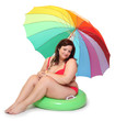Obese woman dressed in swimsuit with beach umbrella.