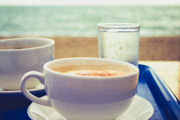 Cappucino and coffee on tray by the sea