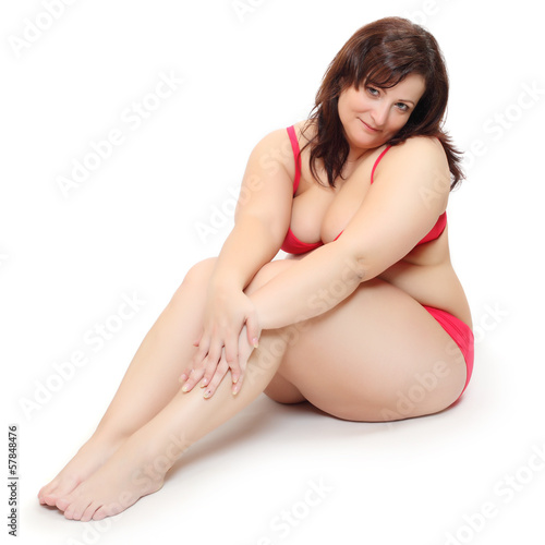 Obese woman dressed in swimsuit sitting on a white.