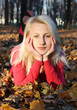 Pretty blond girl posing in autumn park